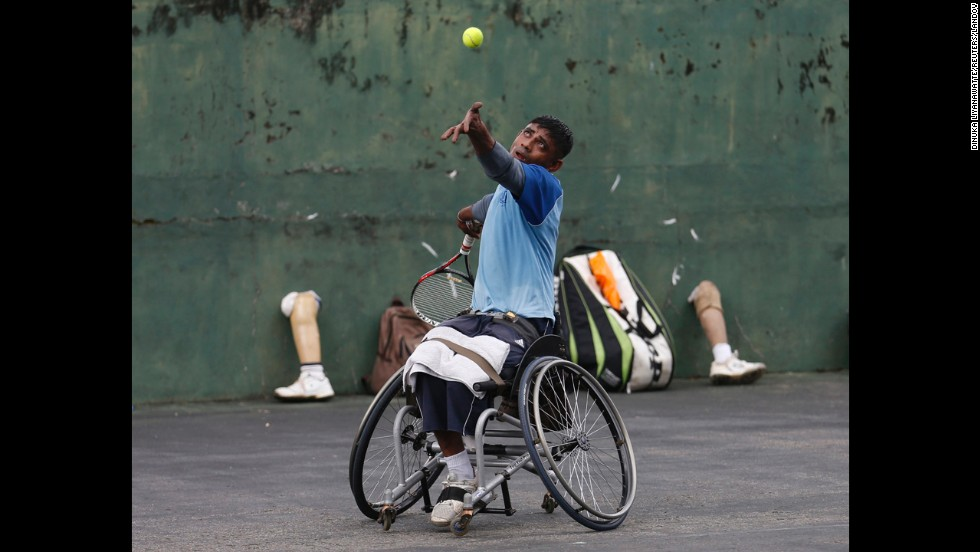Gamini Dissanayake, a member of Sri Lanka's wheelchair tennis national team, serves during a practice session in Colombo on Tuesday, May 6. The team is made up of soldiers who lost their limbs during active duty.