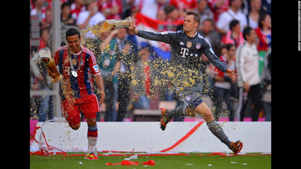 Manuel Neuer of Bayern Muenchen pours beer on teammate Thiago Alcantara as they celebrate after the Bundesliga match against VfB Stuttgart at Allianz Arena in Munich, Germany, on Saturday, May 10.