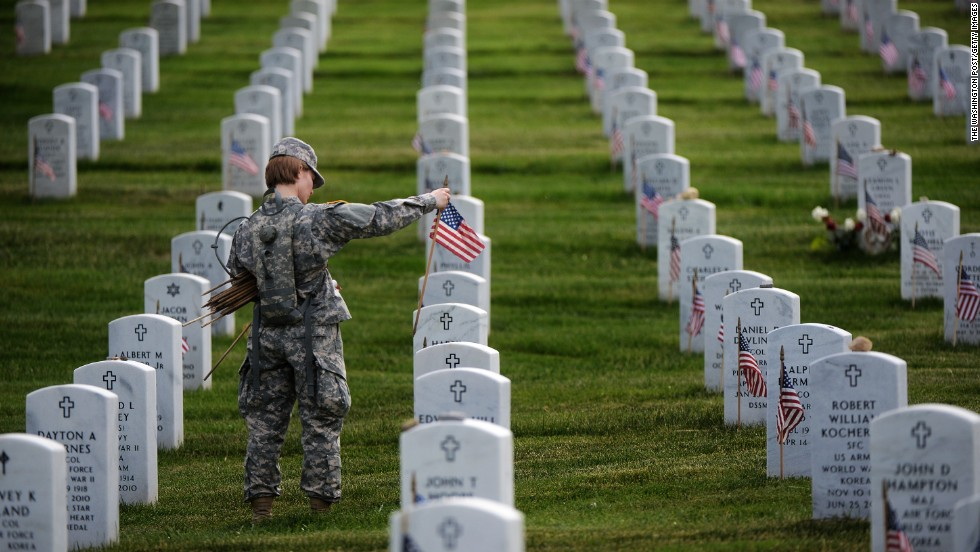 Staff Sgt. Kerrin Kampa, of the Old Guard Fife and Drum Corps, along with other soldiers, place flags in front of headstones at Arlington Cemetery.