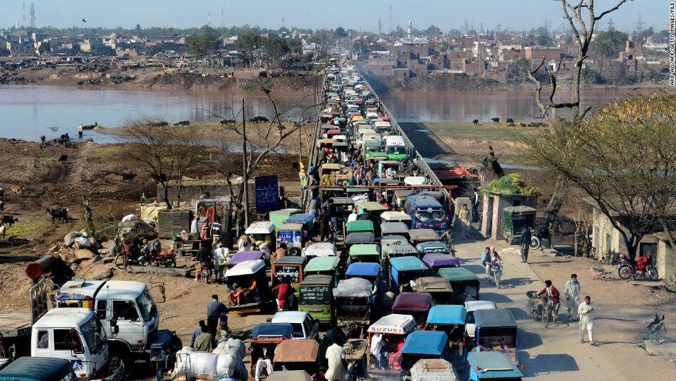 Pakistani commuters, many of them in what are called tuk tuks, or auto rickshaws, wait in traffic as they enter Lahore.