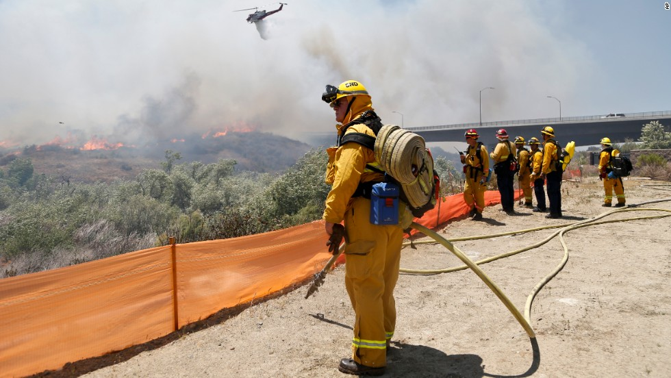 Firefighters watch from a ridge as a helicopter drops retardant on flames in San Diego on May 13.