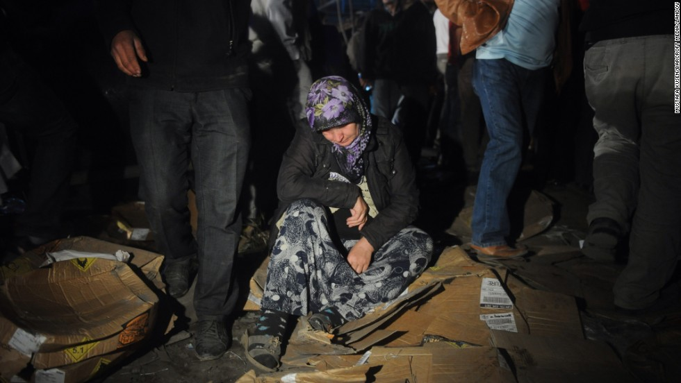 A woman waits on the ground at the disaster scene Wednesday, May 14.