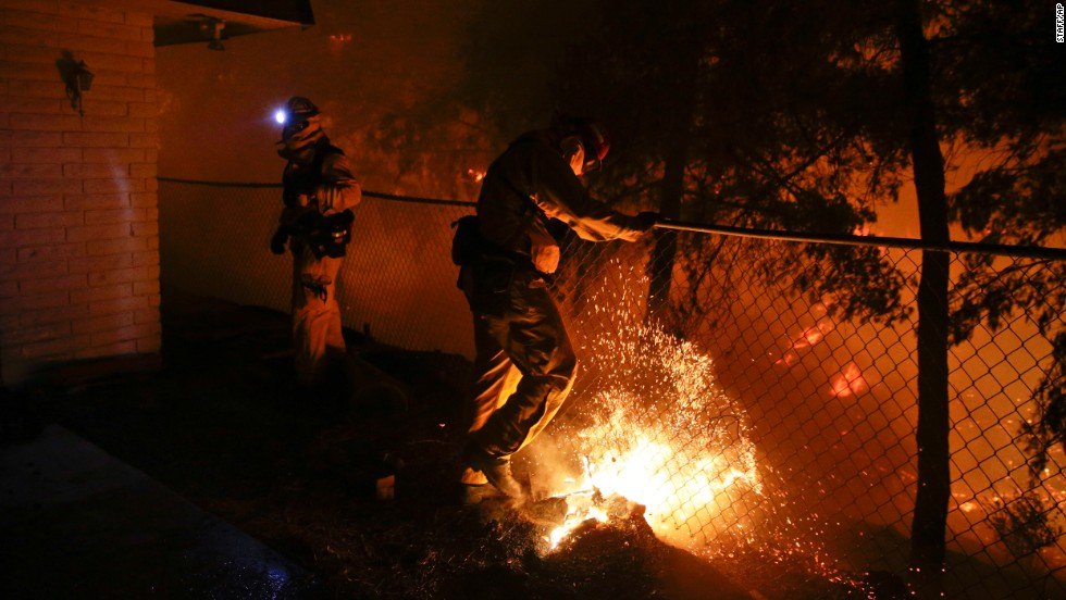 A firefighter puts out a spot fire in San Marcos.