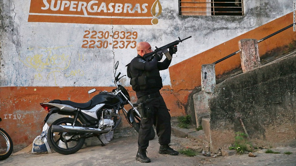 A Brazilian national police officer aims his weapon Tuesday, May 13, during a search for fugitives in the Complexo do Alemao favela of Rio de Janeiro. Brazil is trying to pacify Rio's favelas, or slums, ahead of next month's FIFA World Cup.