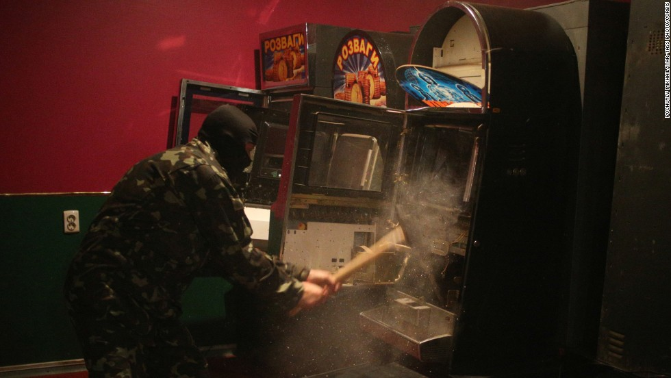 "A member of a ""self-defense"" squad smashes a slot machine with a sledgehammer Monday, May 12, at an illegal club in Slovyansk, Ukraine. Pro-Russian militants are <a href=""http://www.cnn.com/2014/03/26/world/gallery/ukraine-crisis/index.html"">tightening their grip</a> on Ukraine's east and south in the worst East-West crisis since the end of the Cold War."