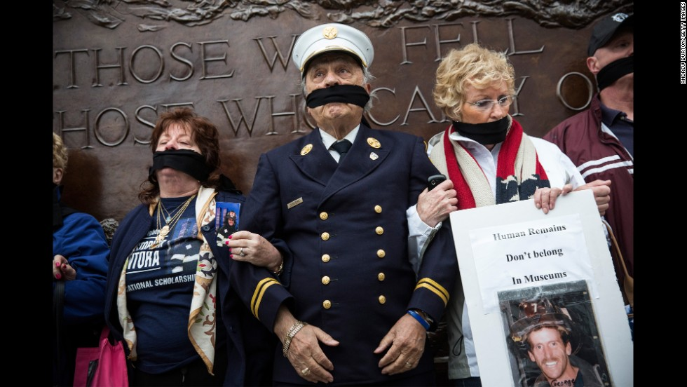 "Al Santora, center, and other family members of 9/11 victims stand together on Saturday, May 10, to protest city officials' decision to keep unidentified human remains at the Memorial Museum in New York. <a href=""http://politicalticker.blogs.cnn.com/2014/05/15/as-obama-visits-911-museum-a-call-to-intervene-in-dispute-over-remains/"">Families who oppose the placement of the unidentified remains</a> have advocated for a separate memorial for their loved ones. They say the underground museum is prone to flooding, and they say the $24 entrance fee is inappropriate for a place akin to a cemetery."