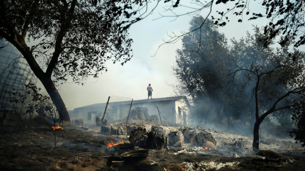 Jeff Brown wets down the roof of his Escondido home as a wildfire smolders around it on May 15.