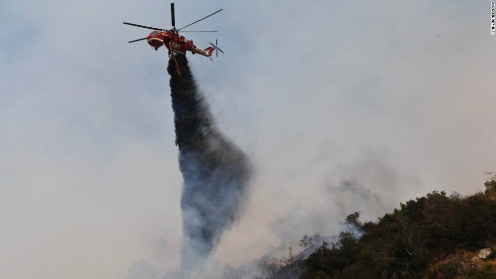 A helicopter drops retardants onto a wildfire May 15 in San Marcos.