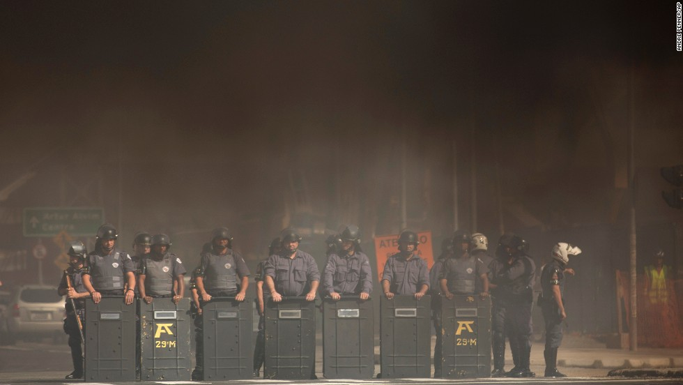 Riot police stand amid smoke coming from burning tires in Sao Paulo on May 15.
