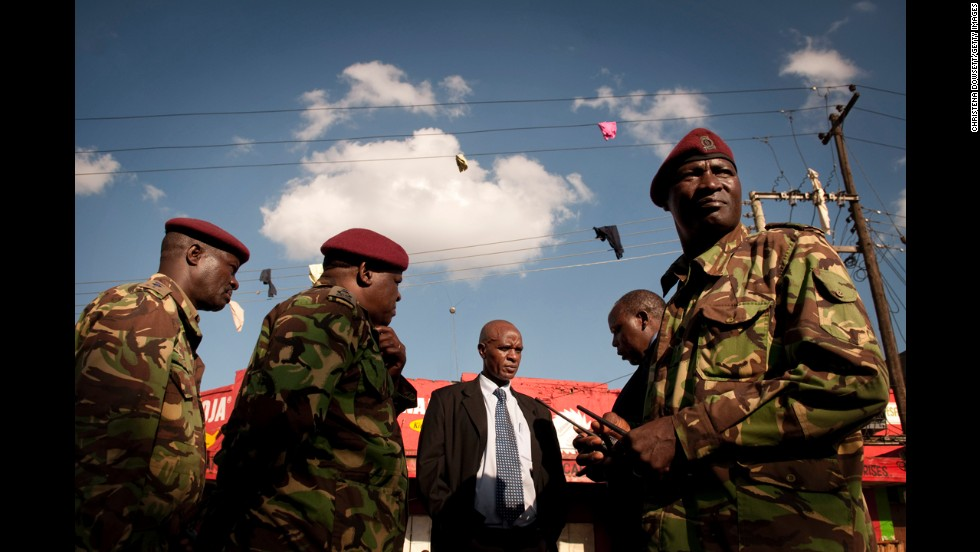 Clothing hangs from a power line May 16 in Nairobi as members of Kenya's General Service Unit confer over the explosions.