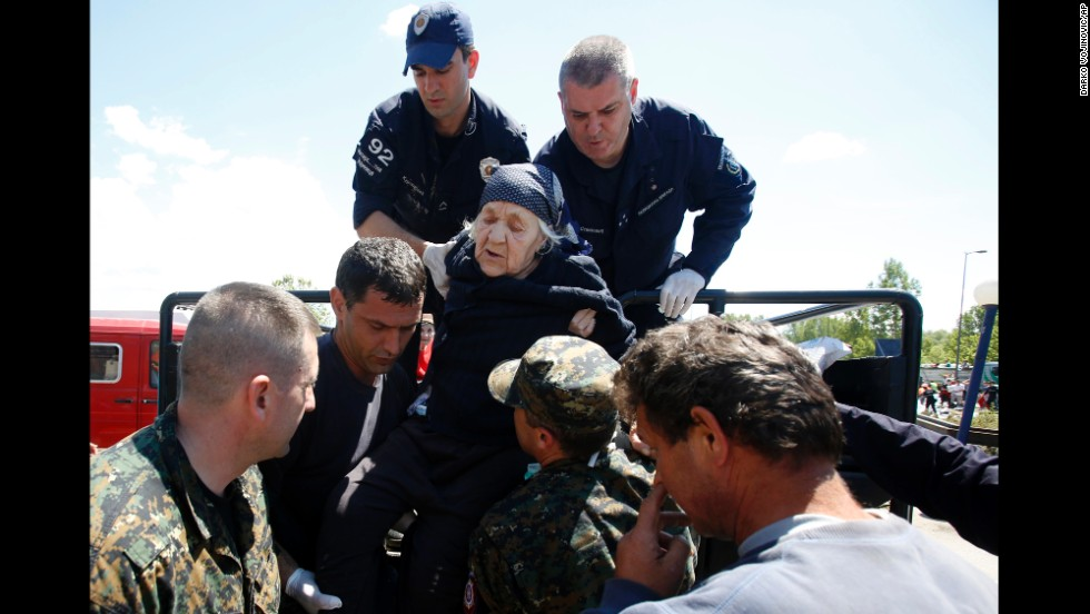Police officers help an elderly women get out of a vehicle in Obrenovac on May 19.