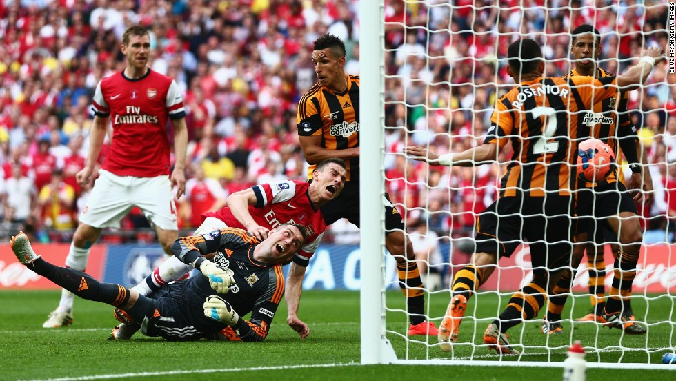 Arsenal's Laurent Koscielny falls over Hull City goalkeeper Allan McGregor as he scores a goal in the FA Cup final Saturday, May 17, in London. Arsenal won the game 3-2, collecting its first trophy since 2005.
