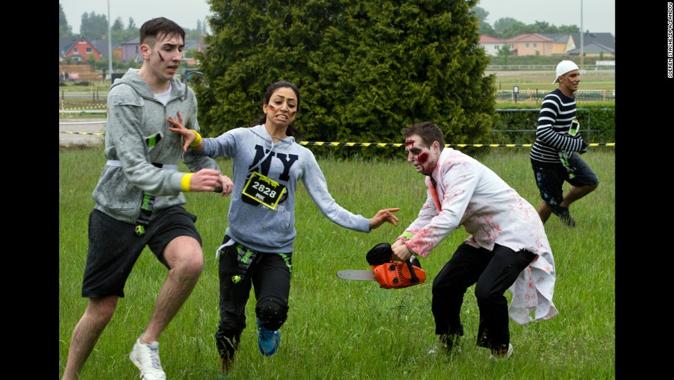 "People dressed as zombies chase runners during the Zombie Run event Sunday, May 18, in Berlin. In the Zombie Run, which is based on the television series ""The Walking Dead,"" runners have to avoid zombies and protect the small flags that are in their belts."