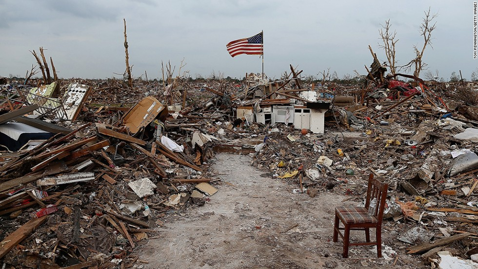 A massive tornado hit Moore, Oklahoma, on May 20, 2013, killing 24 people and causing an estimated $2 billion in property damage. Photographs taken then and now reveal the progress that has been made one year on. Here, an American flag flies over the rubble of a destroyed neighborhood in Moore on May 24, 2013.