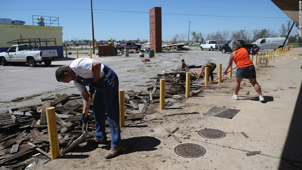 <strong>Then:</strong> Chuck Walker, left, cleans up debris near his shop at a strip mall on June 2, 2013.