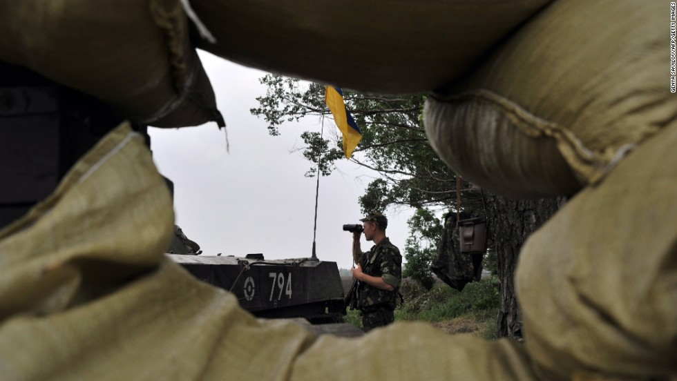 A Ukrainian soldier stands guard on the road from Izium, Ukraine, to Slovyansk on Monday, May 19.