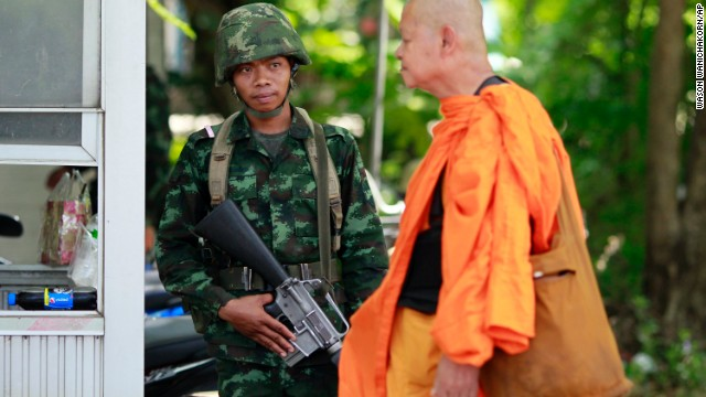 A Buddhist monk walks past a Thai soldier near a pro-government demonstration on the outskirts of Bangkok, Thailand, on Wednesday, May 21.
