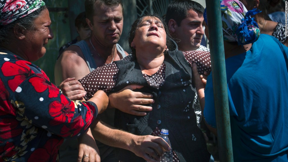 Local citizens help support a woman at a rally protesting shelling by Ukrainian government forces in the village of Semyonovka, Ukraine, on Thursday, May 22.