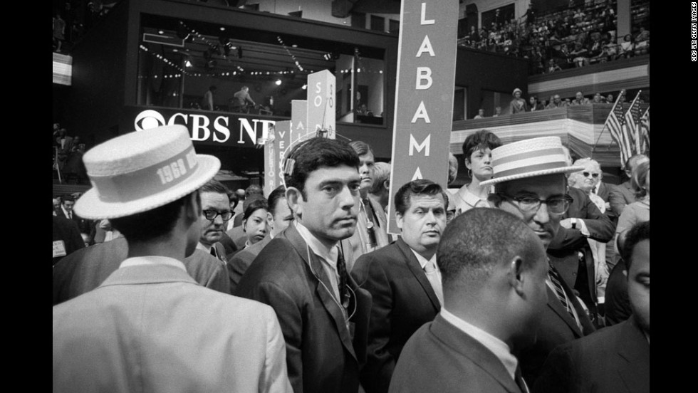 "The 1968 Democratic Convention, held in Chicago, was a scene of chaos both inside and outside the convention hall. At one point, CBS correspondent Dan Rather, center, was treated roughly by security, prompting anchor Cronkite to comment, ""I think we've got a bunch of thugs here, Dan."" Outside, protesters chanted, ""The whole world is watching."""