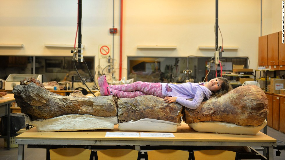 "A girl lies on a large fossilized femur of a dinosaur Sunday, May 18, at the Egidio Feruglio Museum in Trelew, Argentina. Titanosaurs, the dinosaurs unveiled by the museum, might be the largest to ever grace the Earth. <a href=""http://www.cnn.com/2014/05/17/world/gallery/argentina-dinosaur/index.html"">The discoveries</a> were made in Chubut, a remote province of Argentina about 800 miles south of Buenos Aires."