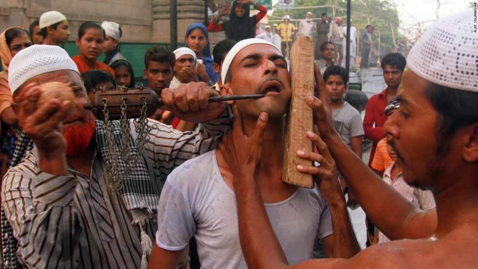 As an act of self-torture, a Muslim man has an iron bar hammered into his cheek during a religious procession in Ahmadabad, India, on Saturday, May 17.