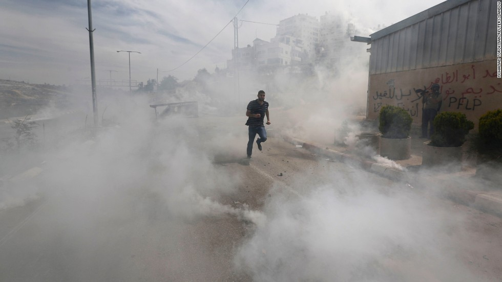 A Palestinian protester runs from tear gas that was fired by Israeli troops Friday, May 16, during clashes near Israel's Ofer Prison in the West Bank.