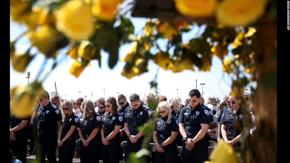 "First responders bow their heads in prayer on Tuesday, May 20, during the remembrance ceremony for those killed by last year's <a href=""http://www.cnn.com/2014/05/20/us/gallery/moore-oklahoma-then-now/index.html"">tornado in Moore, Oklahoma</a>. The tornado killed 24 people and caused an estimated $2 billion in property damage. <a href=""http://www.cnn.com/2014/05/16/world/gallery/week-in-photos-0516/index.html"">See last week in 37 photos</a>"