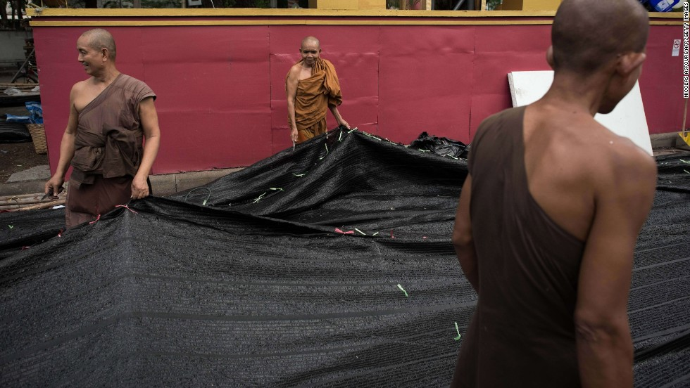 Buddhist monks help dismantle a shade net at an anti-government camp occupied for months in Bangkok on May 23.