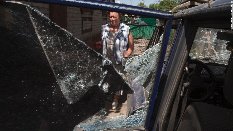 A woman walks past a destroyed car after Ukrainian government forces fired mortar shells during clashes with pro-Russian forces in Slovyansk, Ukraine, on May 23.