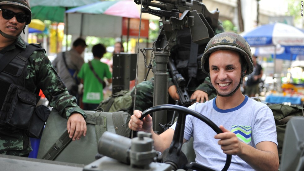 A tourist sits in a Thai army vehicle as soldiers deploy on a downtown street after martial law was declared on Tuesday, May 20.