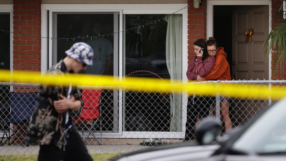 Two women comfort each other Saturday near the scene of a shooting. Seven people also were being treated in a hospital for gunshot wounds or traumatic injuries, a sheriff's office spokeswoman said.