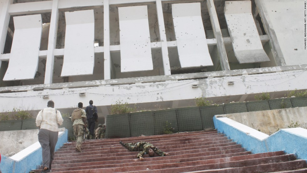 Somali army soldiers walk next to the body of a comrade in front of the parliament building after the attack.
