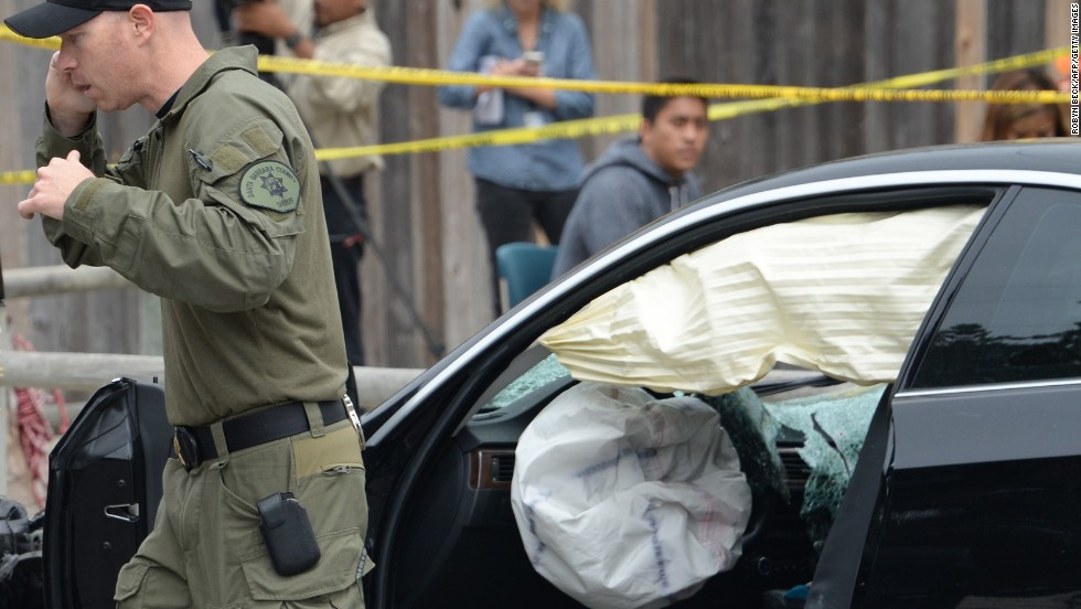 An investigator speaks on a cell phone while examining the gunman's car.
