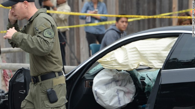 An investigator speaks on a cell phone while examining a the gunman's car.