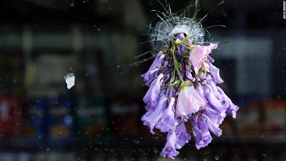 Flowers are placed in a bullet hole in the window of a delicatessen in Isla Vista on May 24.
