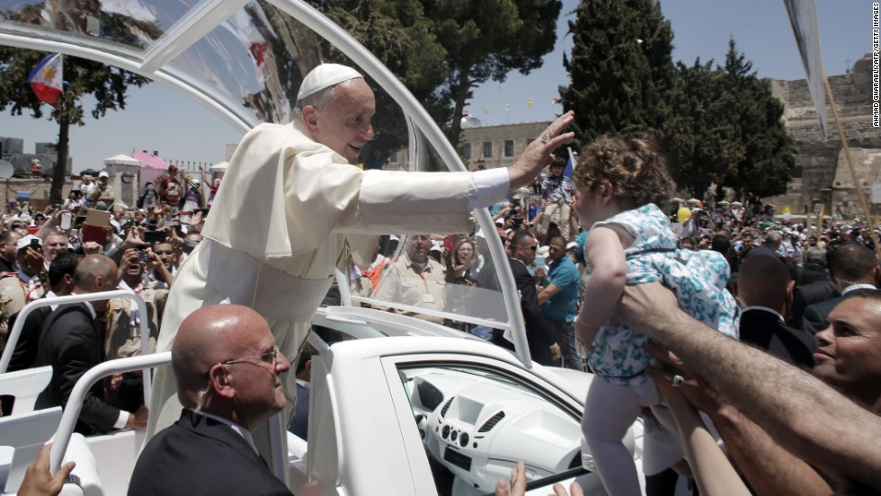 "Francis blesses a child from his Popemobile as he leaves Manger Square after presiding over an open-air Mass in the West Bank town of Bethlehem on May 25. Francis extended an invitation Sunday to the leaders of Israel and the Palestinian Authority to travel to the Vatican for a ""peace initiative,"" as he called for a two-state solution to the intractable conflict."