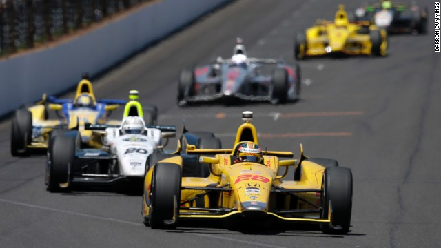 Ryan Hunter-Reay leads Ed Carpenter into the first turn during the 98th running of the Indianapolis 500 on Sunday, May 25.