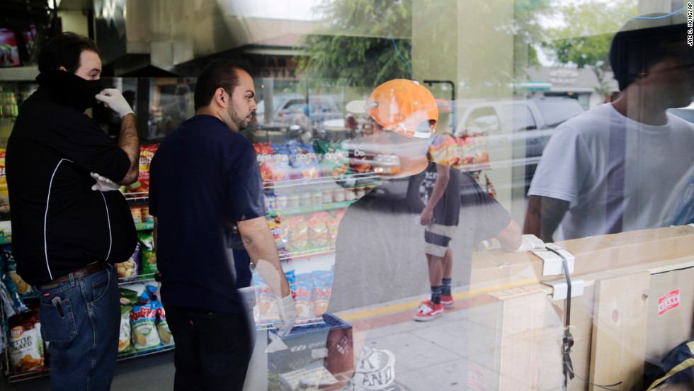 IV Deli Mart owner Michael Hassan, second from left, cleans up his store with employees May 24 as onlookers gather outside one of the shooting scenes. Student Christopher Martinez, 20, was getting a sandwich at the deli when he was fatally shot.