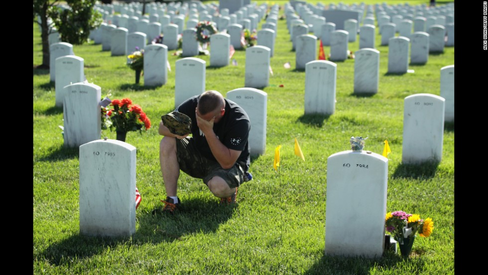 Mike Sunderhaus of Bel Air, Maryland, becomes emotional Sunday, May 25, 2014, as he visits the grave of his friend, Marine Lance Cpl. Jeremiah E. Savage, at Arlington National Cemetery. Savage was killed in 2004 during Operation Iraqi Freedom.
