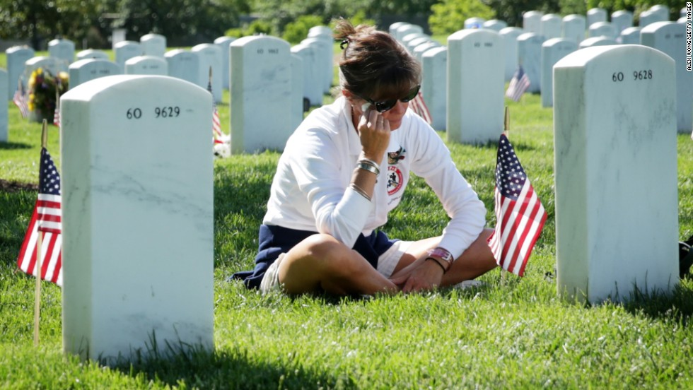 Sarah Greene wipes tears as she visits the grave of her husband, Marine Lt. Col. David S. Greene, at Arlington National Cemetery on May 25, 2014. He was killed in Iraq in 2004.