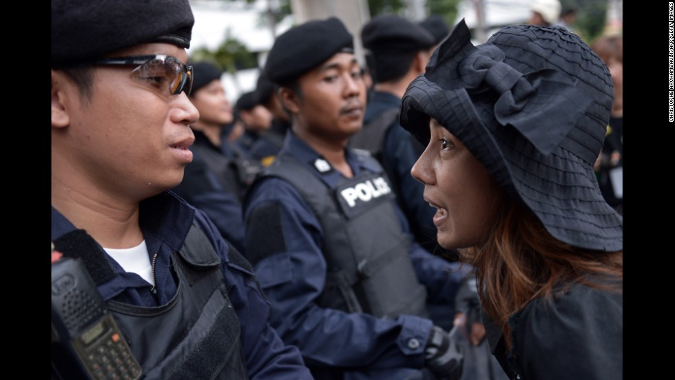 An anti-coup protester faces riot police during a May 26 rally in Bangkok.