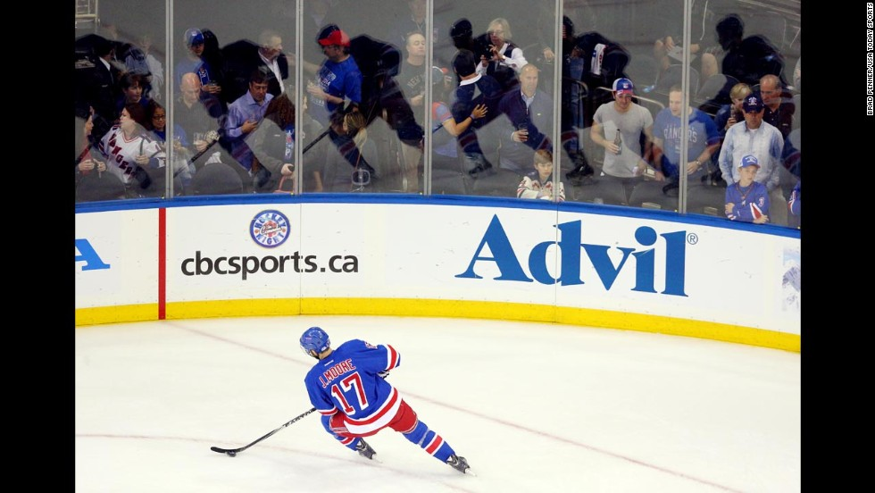 Multiple reflections of New York Rangers defenseman John Moore are seen on the boards as he warms up for Game 4 of the NHL's Eastern Conference finals Sunday, May 25, in New York. The Rangers defeated Montreal in overtime to take a commanding 3-1 lead in the best-of-seven series.