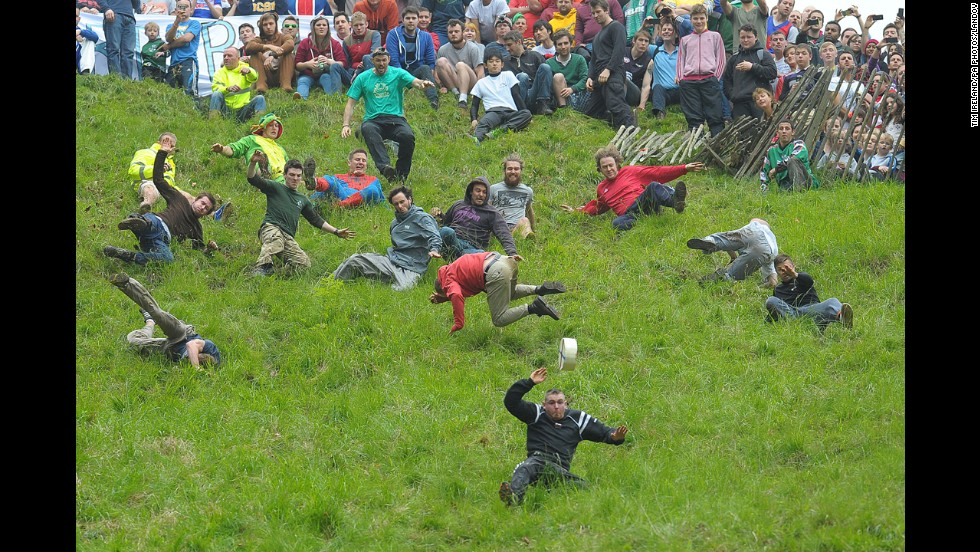 People compete Monday, May 26, in the annual cheese-rolling races at Cooper's Hill in Gloucestershire, England. In the races, runners chase Double Gloucester cheese wheels down an extremely steep hill. The first person over the finish line in each race wins the cheese.