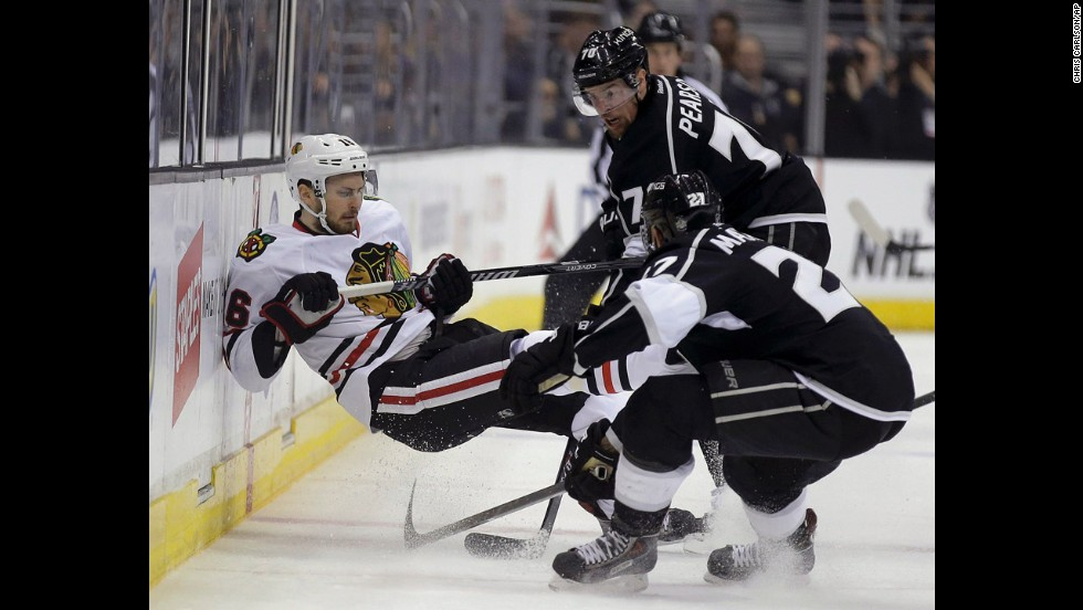 Chicago's Marcus Kruger, left, is checked by Los Angeles' Alec Martinez and Tanner Pearson during Game 3 of the NHL's Western Conference finals on Saturday, May 24. The Kings won 4-3 to take a 2-1 series lead.