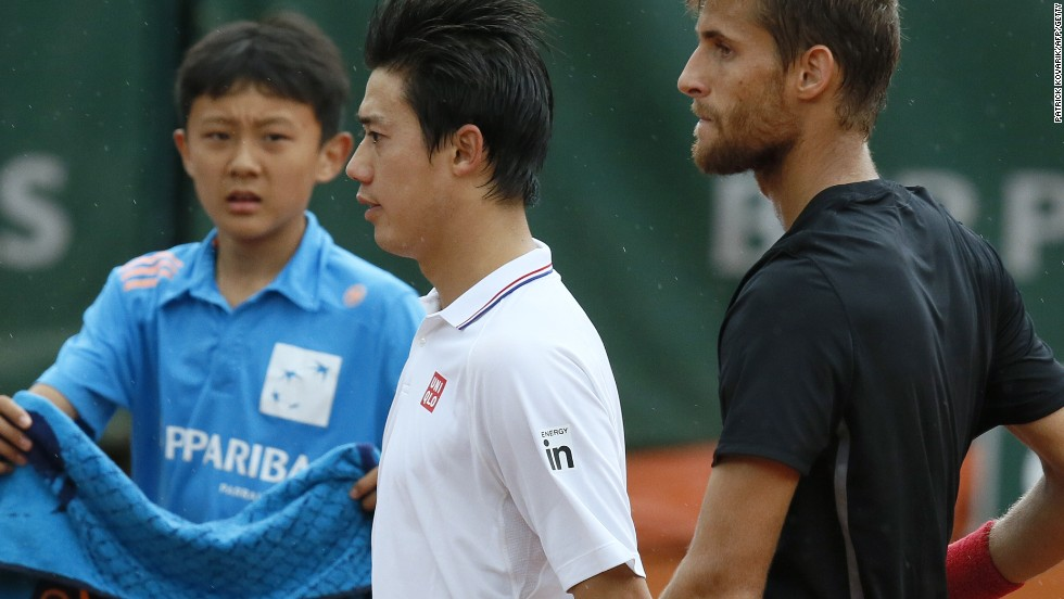 Kei Nishikori of Japan shakes hands with Martin Kluzan (right) after the Slovakian beat him in straight sets in Paris.