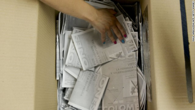 A woman opens a ballot box to start the count at a polling station after presidential elections on May 25, 2014, in Medellin, Antioquia department, Colombia.