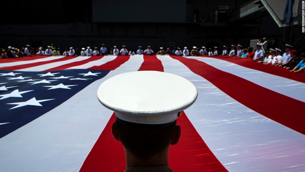 Members of the military unfurl an American flag during a wreath-laying ceremony at the Intrepid Sea, Air & Space Museum in New York on Monday, May 26, 2014.