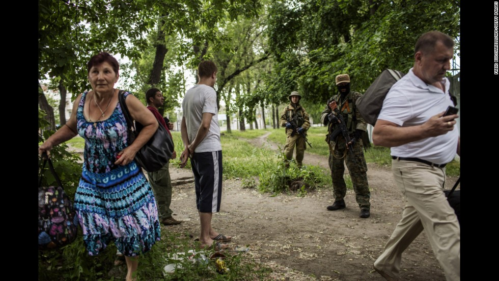 Men stand next to pro-Russian militants as a woman runs away during clashes near the airport on May 26.