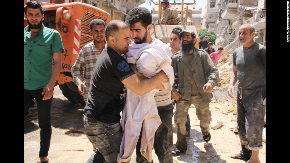 The father of a 3-month-old girl weeps Monday, May 26, after she was pulled from rubble following a barrel-bomb strike in Aleppo.