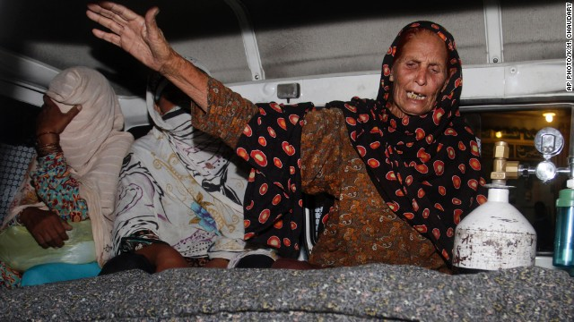 A family member of a pregnant woman who was stoned to death by her own family wails over her dead body in an ambulance at a local hospital in Lahore, Pakistan, Tuesday, May 27, 2014.
